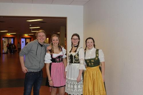 Das Bild zeigt drei Mädchen und einen Jungen aus der 10. Klasse. Der Junge ist normal gekleidet. Die drei Mädchen tragen Dirndl und haben sich die Haare geflochten.