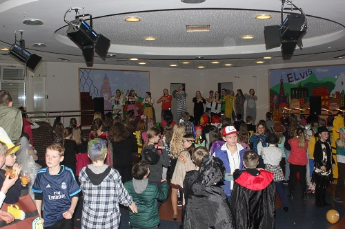 Disco im Forum. Verkleidete Kinder tanzen im großen Bereich. Im Hintergrund etwas erhöht stehen Schülerinnen und Schüler der 10. Klasse und animieren die Kinder zum Mitsingen und Mittanzen.